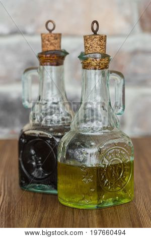 Oil and balsamic vinegar glass bottles with spouts on rustic brick wall background.