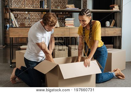 Packing things. Attentive bearded male person bowing head while looking downwards and helping to his girlfriend
