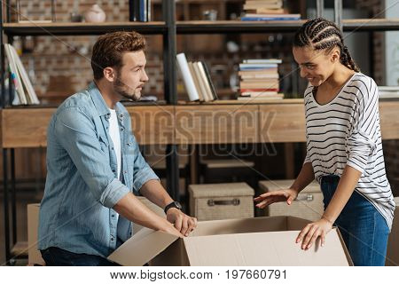 Let do it together. Charming mulatto keeping smile on her face and expressing positivity while gesticulating