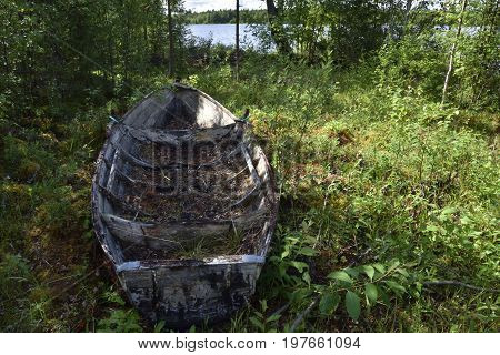 Old abandoned rowing boat standing in shadow with a river in background picture from the North of Sweden.
