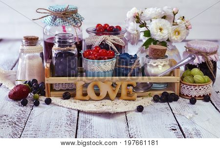 Fresh berry and homemade jam in bottles decorated with cloth, ribbon and flowers. Making fruit jam concept. Summer still life and rustic food vintage background. Preserved fruits.