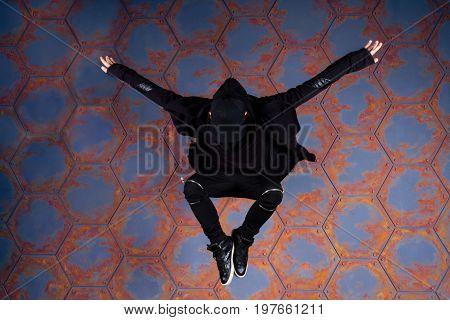 Young dancer jumping high near the urban wall.