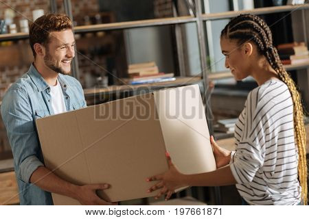 Removing package. Attractive male person keeping smile on his face and holding box in both hands while feeling happiness