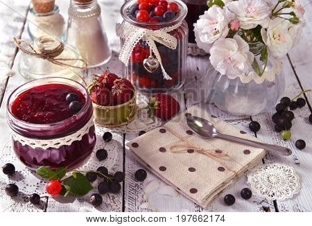 Black currant, strawberry and cherry jam with roses, vintage jars and spoon. Making fruit jam concept. Fresh berry on wooden table, summer still life and rustic food background. Preserved fruits