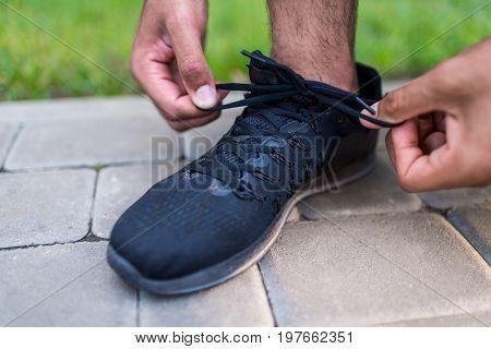 cropped shot of sportsman tying shoelaces on sneaker outside