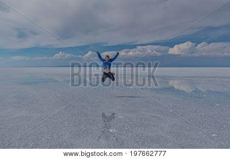 Uyuni, Bolivia- March 25, 2017: Man jumping on the lake Salar de Uyuni Bolivia