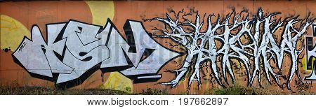 A Photo Of Several Graffiti Artworks On The Metal Wall. Graffiti Drawings Are Made With White Paint