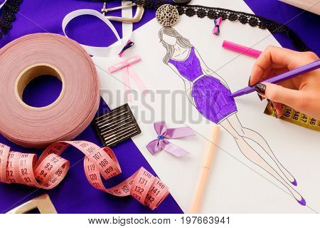 Dressmaker's workplace: buckle ribbons lace needles sketch fabric measuring tape and band. Girl sketching a dress