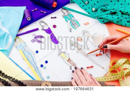 Dressmaker's workplace: spools pencils sketch fabric measuring tape and ribbons. Girl drawing sketches of dresses poster