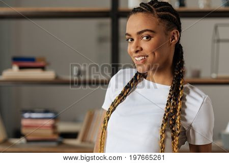 Expressing positivity. Pretty smiling female standing in her room and expressing positivity while looking at camera