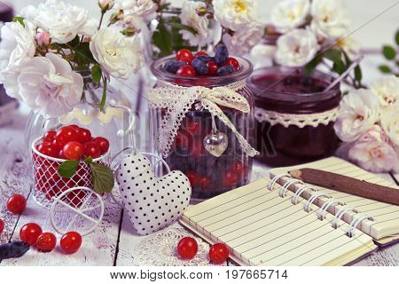 Open notebook with copy space, vintage jars with cherry and honey berry and homemade jam. Making fruit jam concept. Fresh berry on wooden table, summer still life and rustic food vintage background