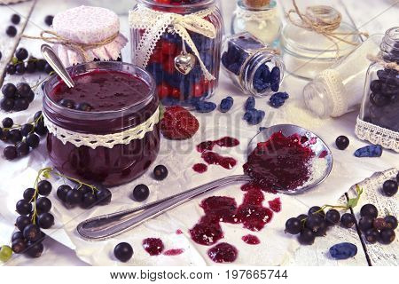 Making jam of black currant berry and honeysuckle berry with vintage jars on the table. Fresh berry on wooden table, summer still life and rustic food vintage background. Preserved fruits