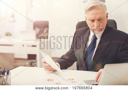 Dedicated worker. Professional intelligent ambitious businessman analyzing a report while perusing something on his computer and holding a sheet of paper
