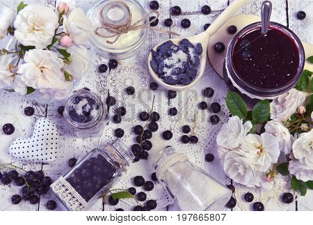 Making fruit jam concept with sugar, fresh berry, glass jars, spoon and roses on the table. Fresh berry on wooden table, summer still life and rustic food vintage background. Preserved fruits