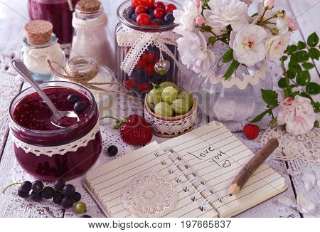 Vintage jar with jam, fresh berries and notebook with text love you. Making fruit jam concept. Fresh berry on wooden table, summer still life and rustic food background. Preserved fruits