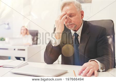 You have to focus. Tired worried busy man having a severe headache while working on important project and spending long hours in the office