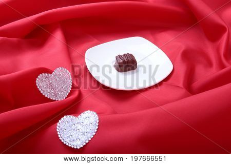 delicacy handmade chocolate pralines and decoration heart on white saucer