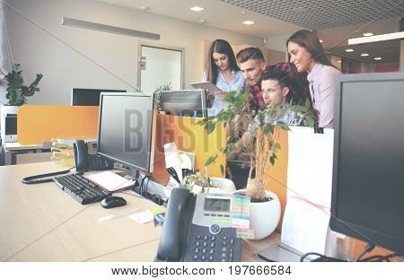 Group of young modern people in smart casual wear having a brainstorm meeting while standing in the creative office