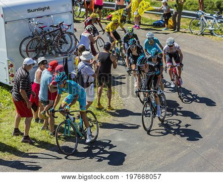 Col du Grand ColombierFrance - July 17 2016: Group of cyclists riding on the road to Col du Grand Colombier in Jura Mountains during the stage 15 of Tour de France 2016.