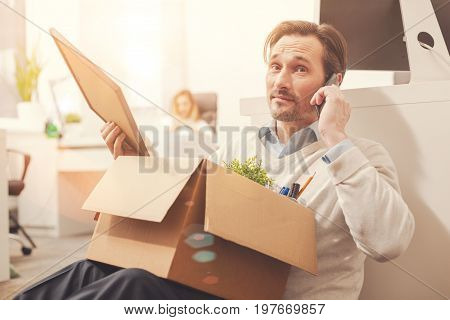 Can you help me. Tired troubled fired employee sharing bad news with his friend as he packing the things before leaving the office