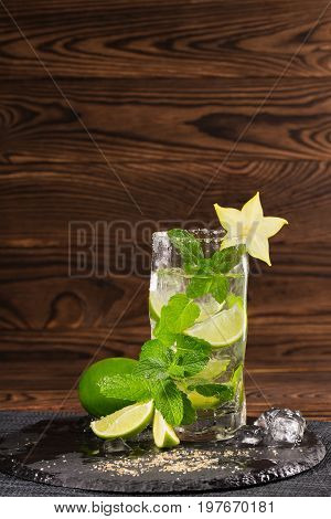 Refreshing mojito beverage with rum, fresh lime, mint, crushed ice and carambola on a dark wooden background. A glass full of alcohol drink on a dark table-cloth. Summer non-alcohol drink. Copy space.