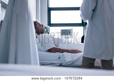 Sick man lying in hospital bed with doctor. Male patient getting treatment in hospital.