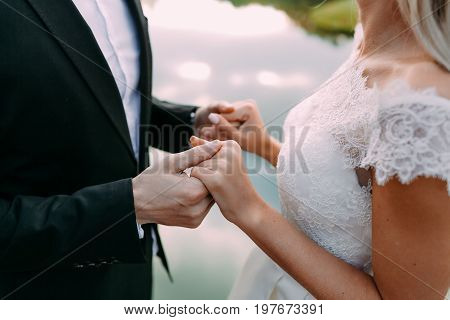Wedding. Beautiful bride and groom are holding hands. Side view of young couple standing face to face and looking at each other while standing against the lake. Close-up