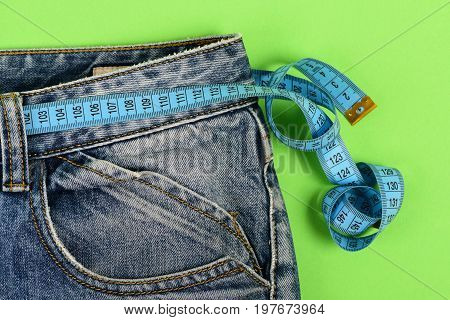 Blue jeans with blue measure tape instead of belt. Upper part of denim trousers isolated on green background. Close up of jeans with measure tape around waist. Healthy lifestyle and dieting concept.