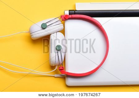 Earphones In Red And White Colors With Computer. Music Concept
