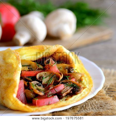Homemade omelette filled with fresh tomato slices, fried mushrooms and chopped dill. Stuffed summer omelette recipe. Healthy food. Closeup