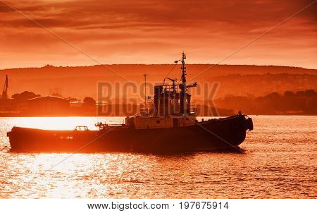 Black Sea Port At Sunset. Tug Boat Is Underway