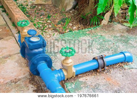 valves water brass with knob green at connection joint old pipe steel paint blue. on the cement floor outside of the Industrial buildings