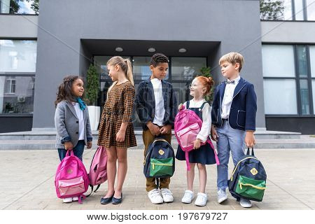 Group Of Adorable Multiethnic Schoolchildren Holding Backpacks And Looking At Each Other Near School