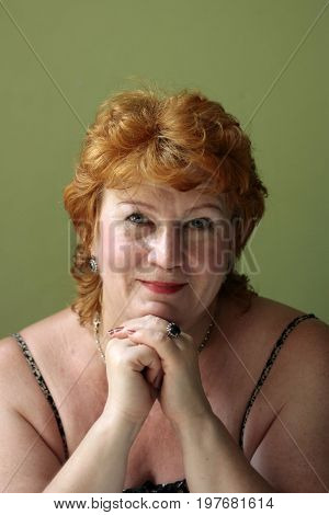 Portrait full face of a well-groomed and cheerful woman middle-aged with red hair fingers touch the chin and looks straight into the lens