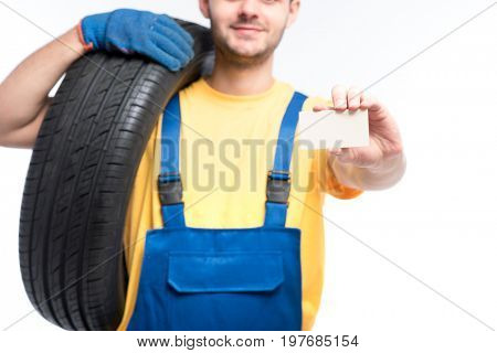Worker holds tire and empty businesscard in hands