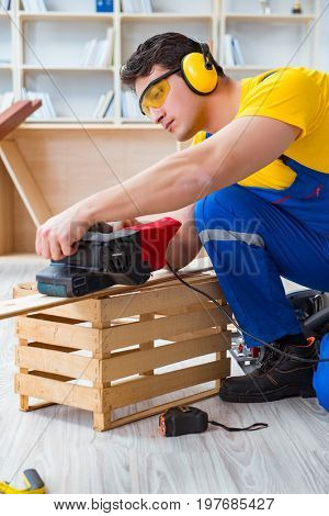 Repairman carpenter polishing a wooden board with an electric po