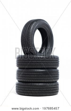 Pile of unused car tires on white background