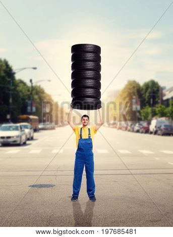 Service worker holds pile of tires over head