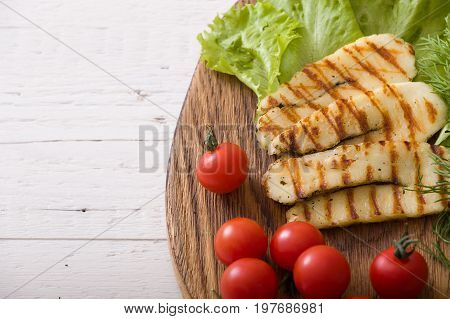 Grilled slices of homemade halloumi cheese with green salad fresh herbs and organic tomatoes. Fried halloumi cheese with grill marks on wooden background top view close-up
