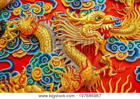 Chinese carving art of golden dragon decorated on wall of Chinese shrine.https://www.bigstockphoto.com/account/uploads/contribute?edit=197686987#categories