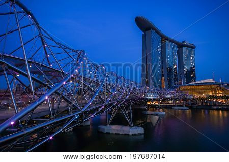 SINGAPORE - JUNE 17 2014 : Bridge to Marina Bay Sands Hotel during twilight time in Singapore