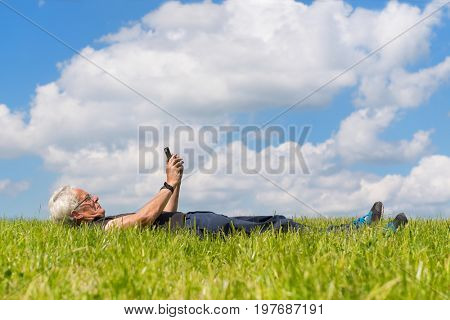 Senior man laying in nature with mobile phone