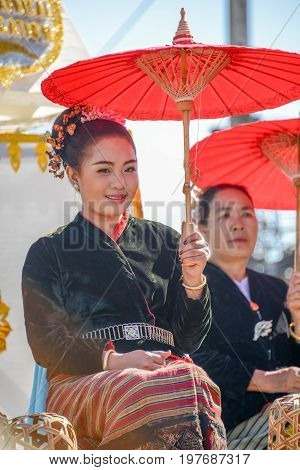 CHIANGMAI THAILAND - JANUARY 25 2015: Indigenous girl holding red paper umbrella in parade of 22nd Traditional Skirt Fabric and The Indigenous Product and Culture Festival in Mae Chaem Chiangmai Thailand