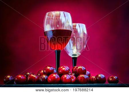 Cherry juice, wine or liquor concept. Glass with red wine and ripe fresh  berries on a table. Alcohol drink.