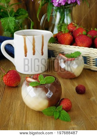 Sauce made of two sorts of chocolate on a wooden background and strawberries in the background