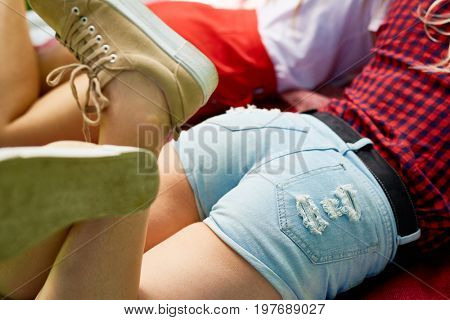 High angle closeup of cute young girls bootie in short jeans shorts lying next to her friend on blanket outdoors