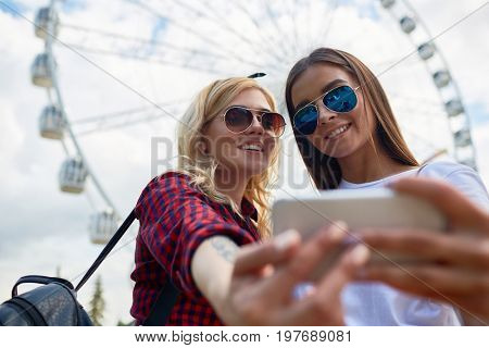 Portrait of two beautiful young girls taking selfie via smartphone camera standing against tall Ferris wheel in amusement park