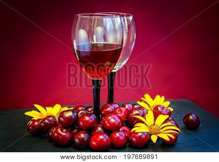 Cherry juice, wine or liquor concept. Glass with red wine, ripe fresh  berries and yellow summer flowers on a table. Alcohol drink.