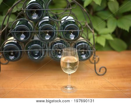 Front shot of the wine glass in focus and a metal bottle holder in the blurred background