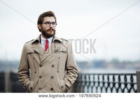 Pensive young man in beige trenchcoat hanging around outdoors